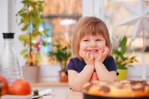 A young girl smiling widely in a kitchen