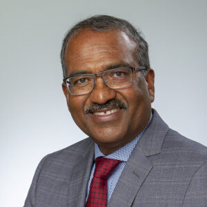 Raja has a big smile and thin wire glasses. He is wearing a grey blazer with a red patterned tie over a white and blue shirt.