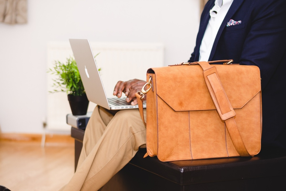 A man working on his laptop with a vegan briefcase beside him