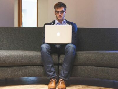 Man sitting at the sofa while surfing his apple laptop