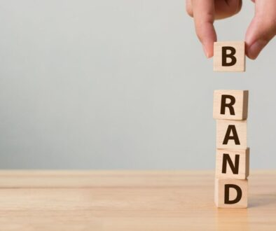 "A stack of wooden cubes that spells the word ""brand"" representing how branding builds small businesses."