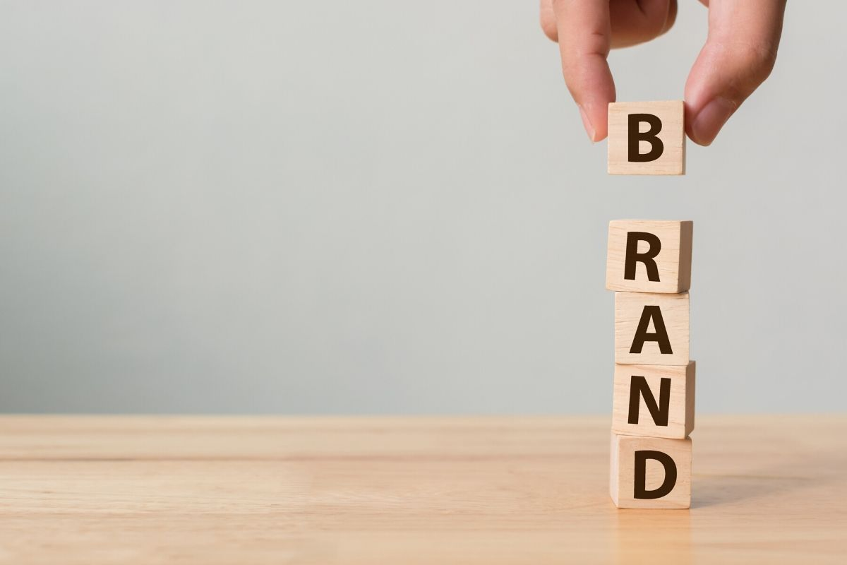 """A stack of wooden cubes that spells the word """"brand"""" representing how branding builds small businesses."""