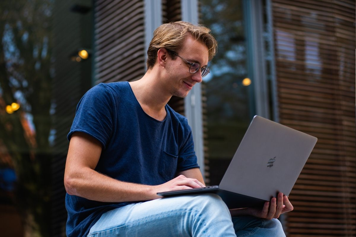 Someone looking at his laptop searching for online business ideas.