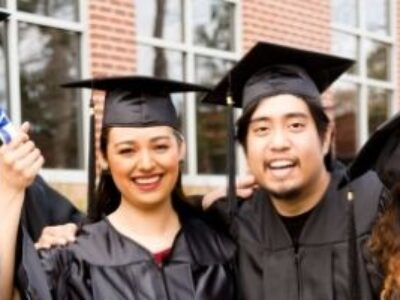 Six multi-ethnic friends dressed in cap and gowns excitedly show off diplomas after college graduation.