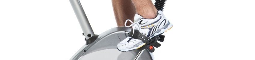 Foot of a man wearing sneakrs while paddling the bike