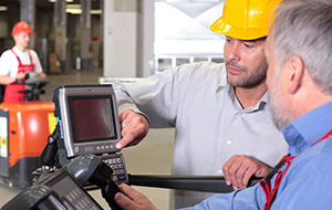 two workers with control panel in factory, third one on forklift