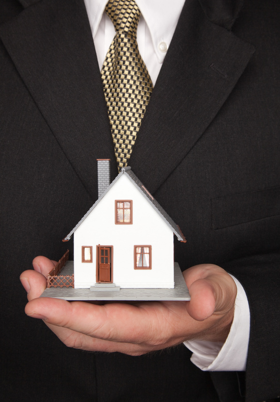 man in business suit holding a model house in his hand