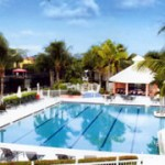 Florida community swimming pool with cabana and palm trees