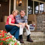 Portrait Of Happy Senior Couple Sitting Outside House With For Sale Sign