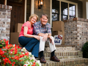 Naples on list of Great Places to Retire by Kiplinger Magazine - Portrait Of Happy Senior Couple Sitting Outside House With For Sale Sign