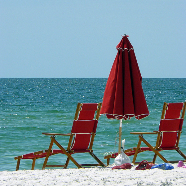red chairs and umbrella on the beach in Naples, Florida