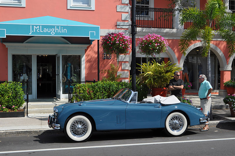 Two men talking on sidewalk in Naples, Florida, vintage convertible car in foreground