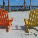 Naples Reserve lake beach - orange and yellow chairs facing the lake