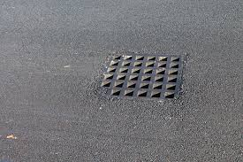 Installed square catch basin in a freshly paved asphalt parking lot