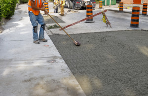 Contractors brush finishing while installing a new concrete repair project