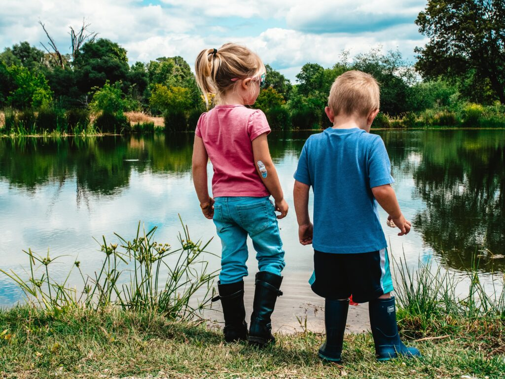 Image of a little girl and boy enjoying nature at a pond.