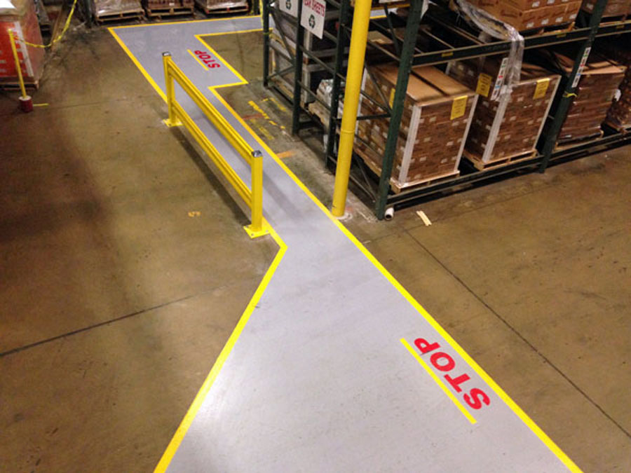 Pedestrian walkway on warehouse floor with Stop markings