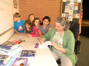 Signing books for students at The Branch School.