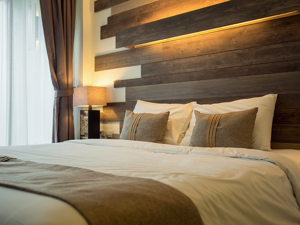 Empty double bed and lamp on side of bed in luxury and natural style bedroom is decorated with wooden boards.