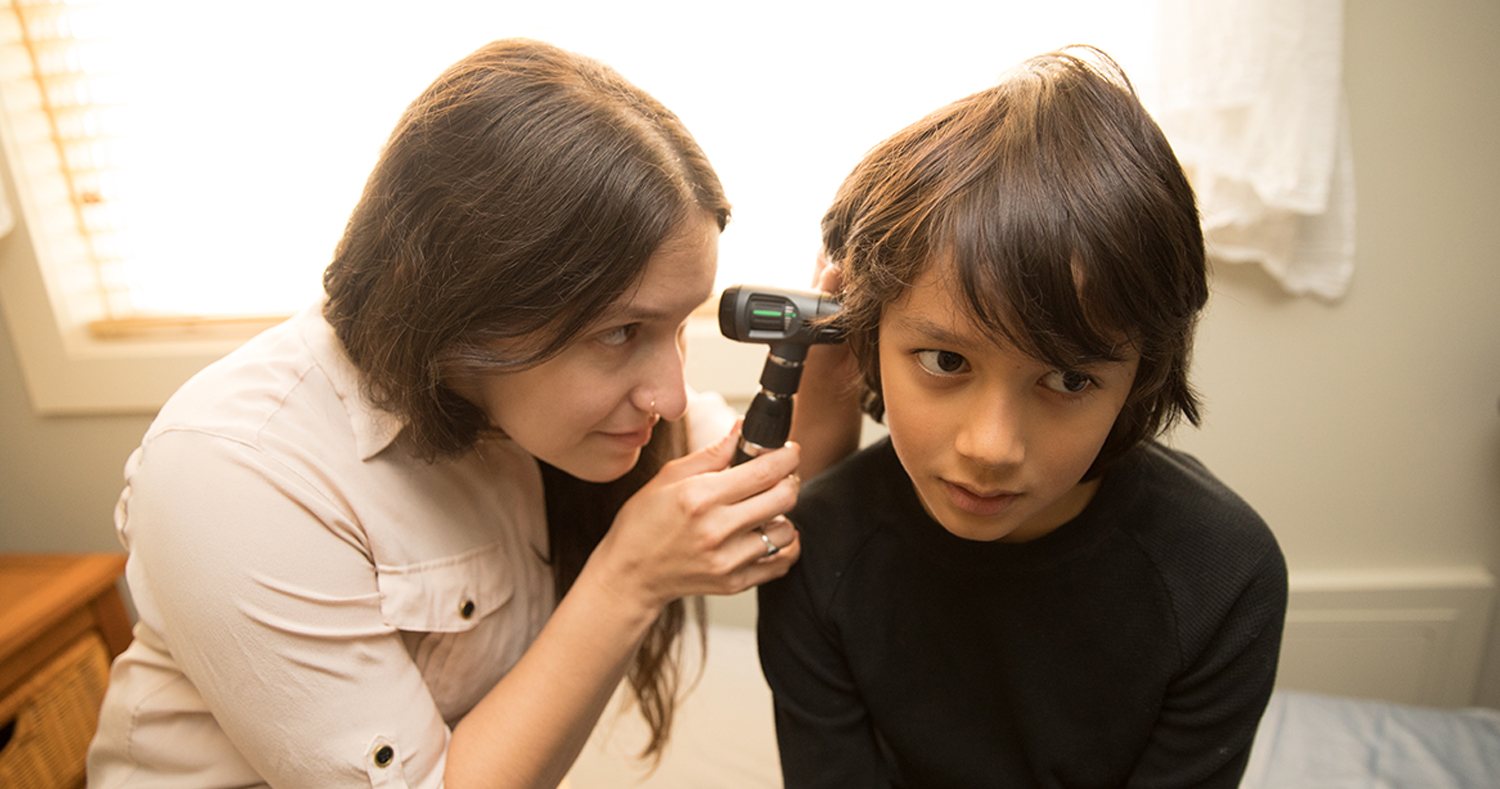 naturopathic in pediatric visit doing ear exam with boy