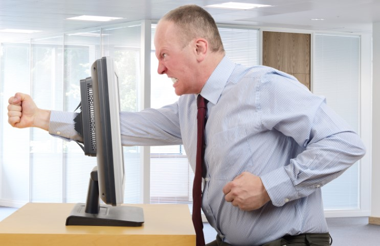 Businessman in office in a rage with a computer screen