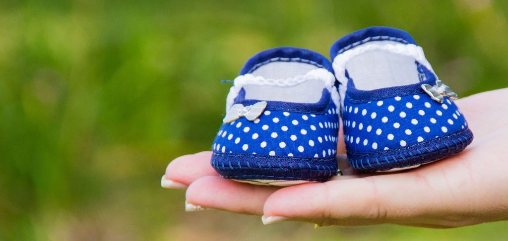 Close-up of cute dark blue polka dot baby shoes with lace bows nesting on the palm of a young woman suspects she's pregnant as she shows pregnancy symptoms.
