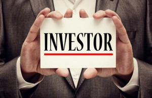 Investor Visas - Man holding sign with INVESTOR in capital letters with red underline.