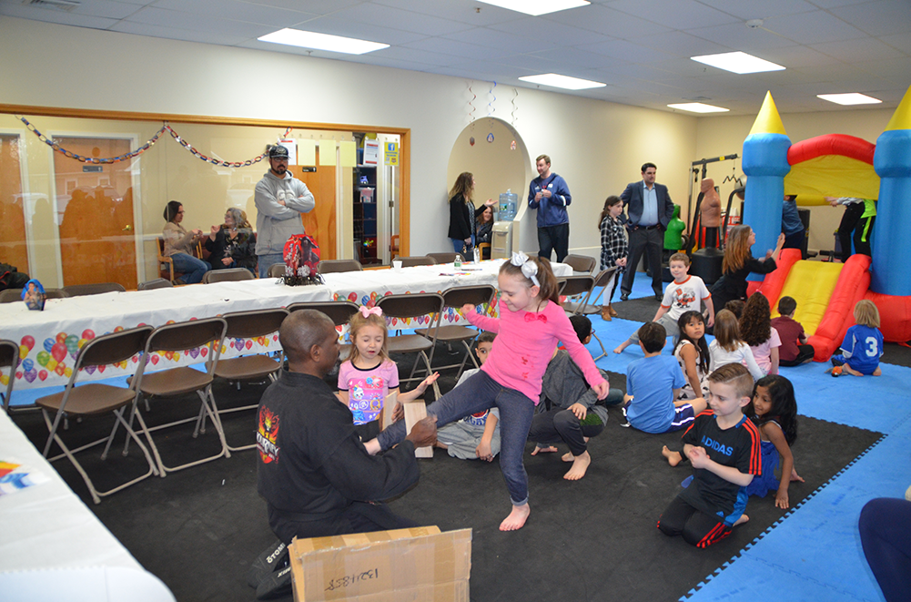 Kids at karate dojo birthday party are breaking boards and jumping in a bounce house
