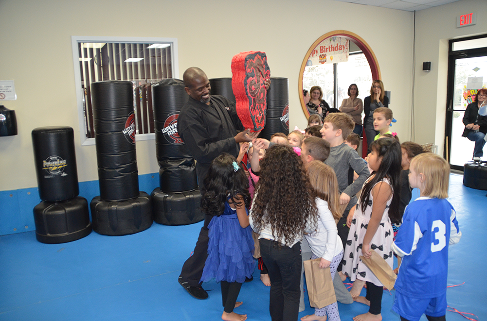Kids at karate birthday party are surrounding karate master who is holding a Piñata