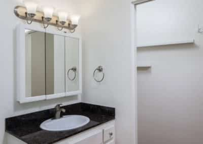 Bathroom with white cabinets and black countertop