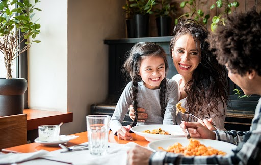 a woman and a child smiling at a man having a meal