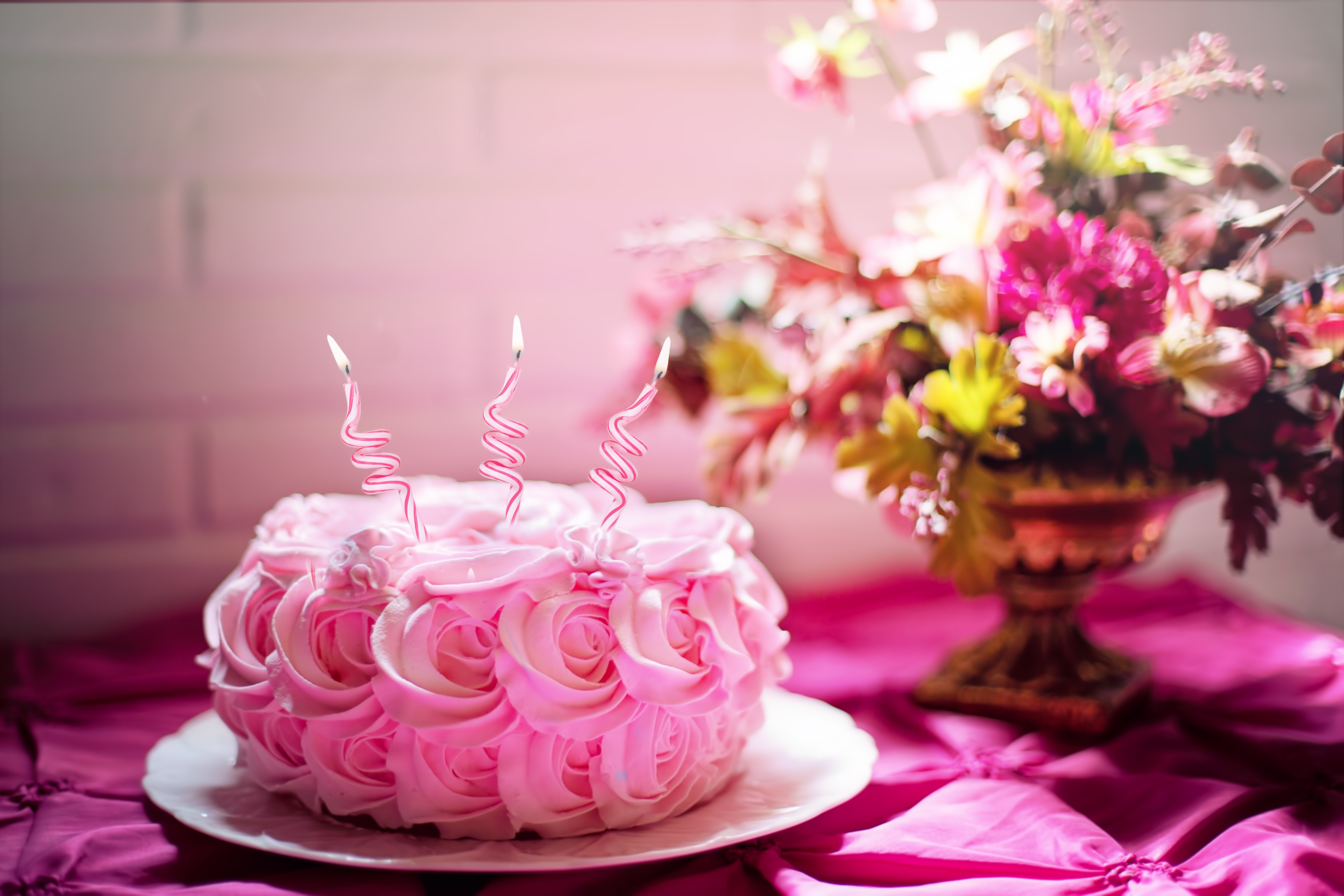 pink flower cake with candles and a bouquet