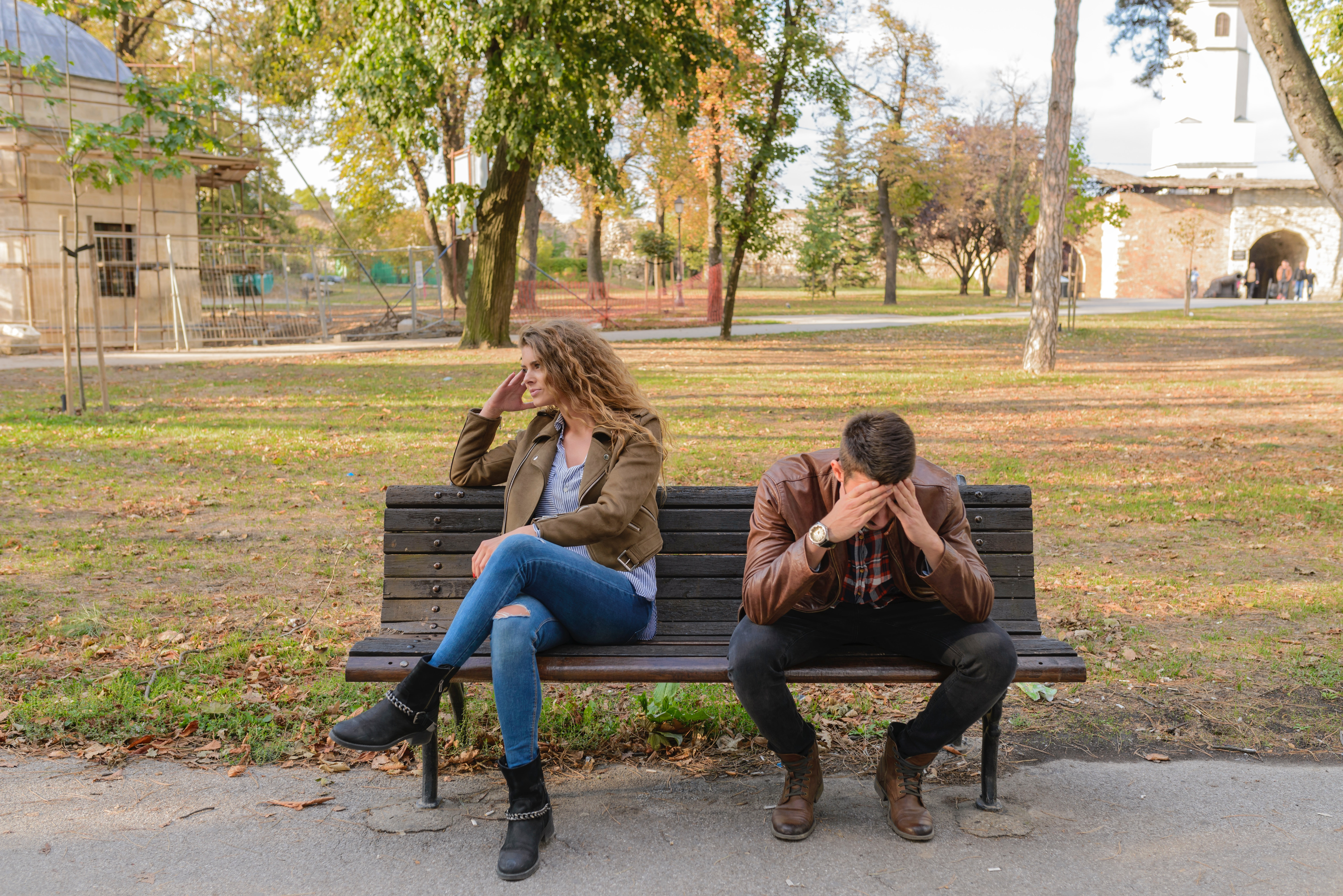 couple sitting on a bench after a fight