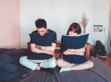 sad couple sitting on a bed holding pillows