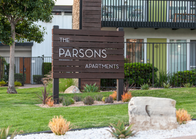 The Parsons apartment homes entrance with sign and landscaping