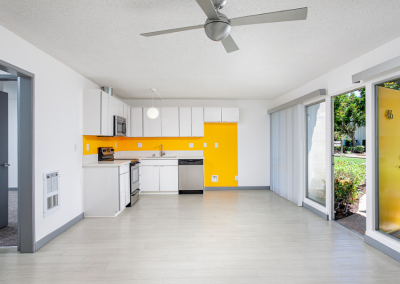 Empty kitchen and living room with bright yellow wall and white cabinets