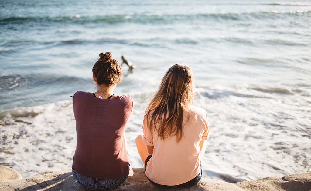 Two girls sitting by the ocean