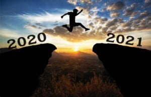 A young man jump between 2020 and 2021 years over the sun and through on the gap of hill silhouette evening colorful sky.