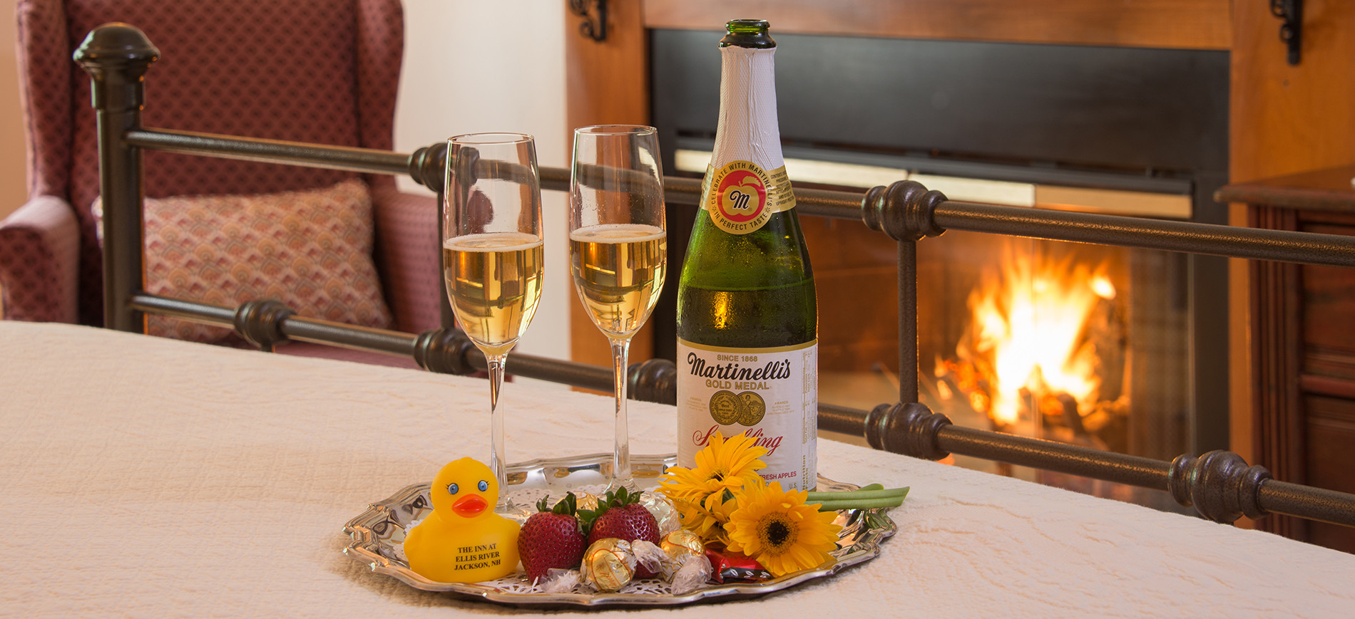 Glasses & bottle of cider on silver tray with rubber duck, strawberries, chocolates. Tray on bronze bed with fireplace behind