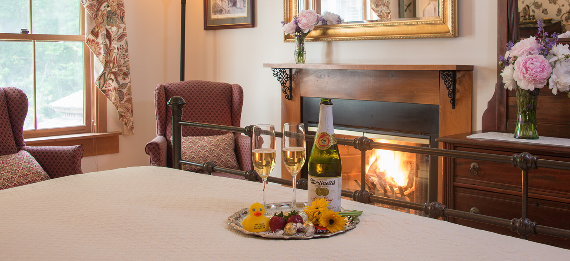 Silver tray with cider glasses & bottle, rubber duck, chocolates on king bed with chairs & fireplace behind