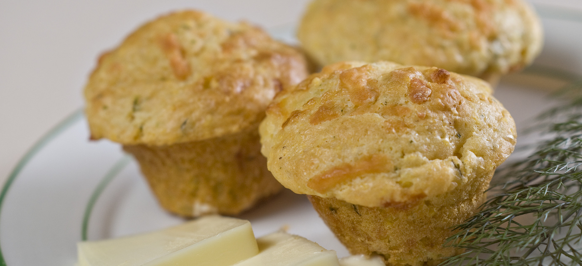 Three dill cheddar muffins with butter pats & fresh dill sprigs