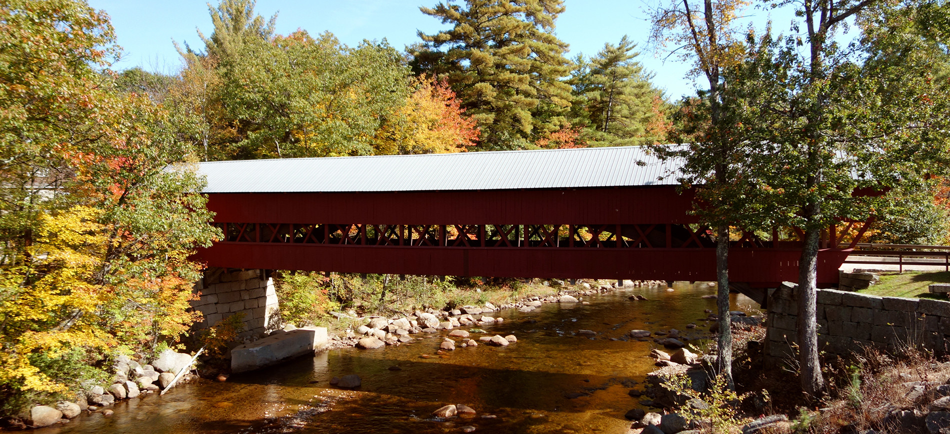 Covered Bridge in NH over river with foliage around it