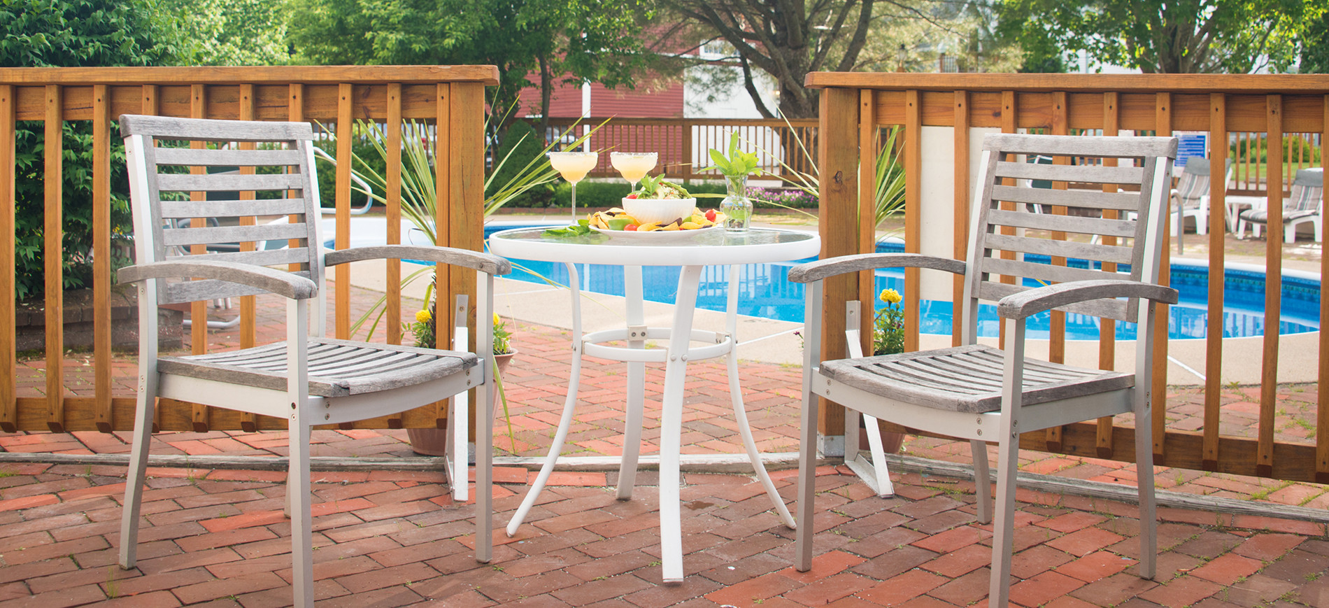 patio with two chairs & table with drinks, fence and pool behind
