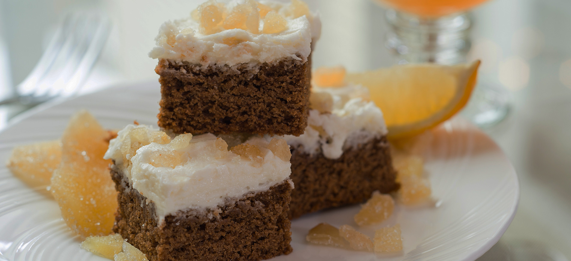 Three stacked pieces of gingerbread with lemon frosting in front of glass mug of cider