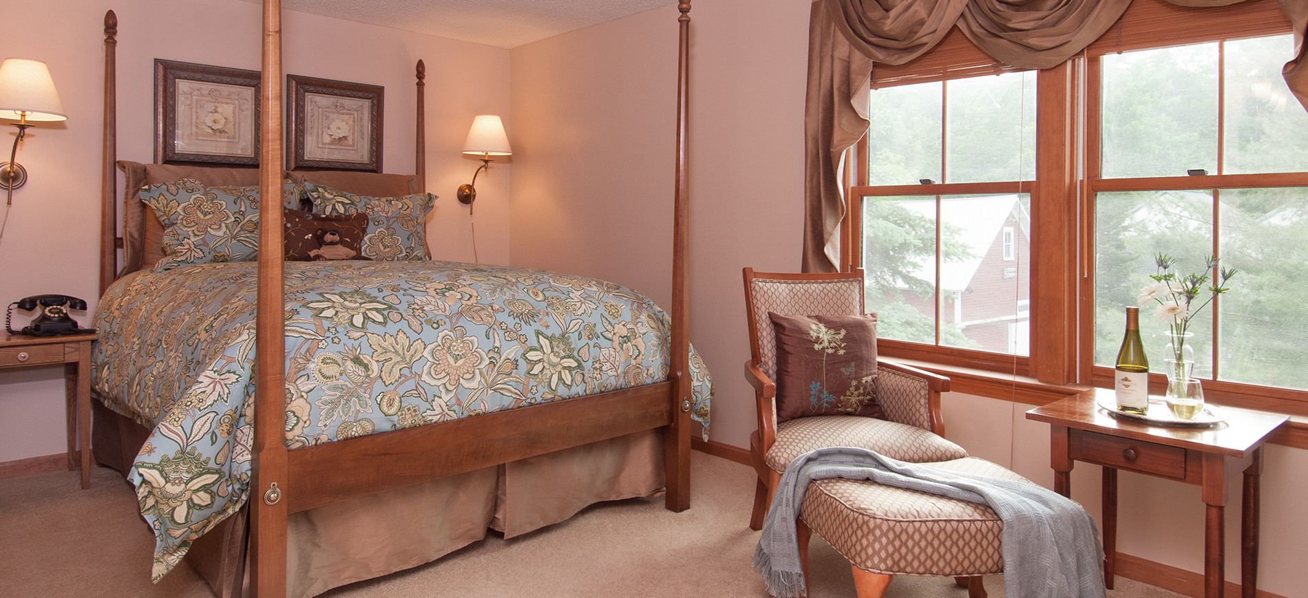 queen four poster bed with aqua & beige bedding, wall lamps on each side of bed, beige arm chair with ottoman, aqua shawl, table with wine & flowers