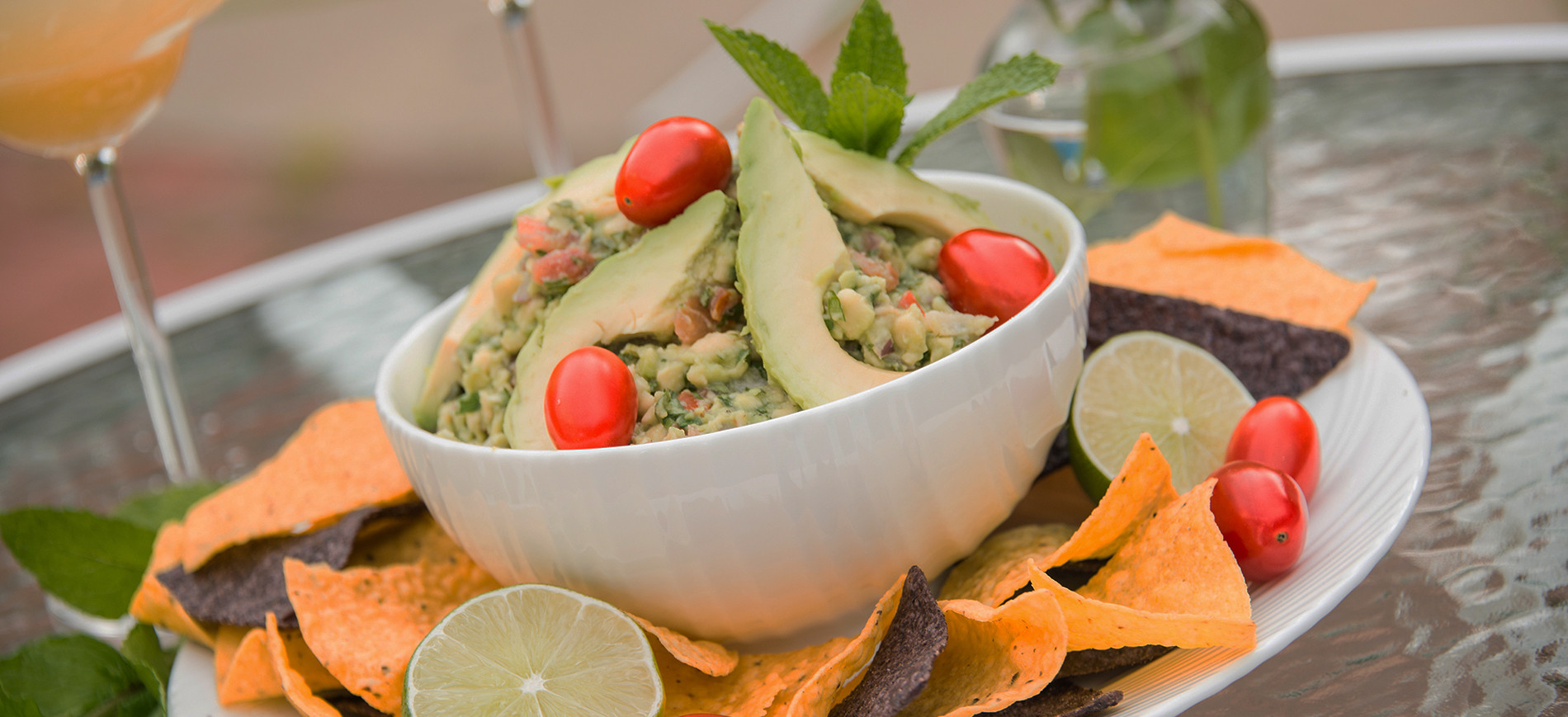 Guacamole with cherry tomato garnish in white bowl surrounded by yellow and blue corn chips