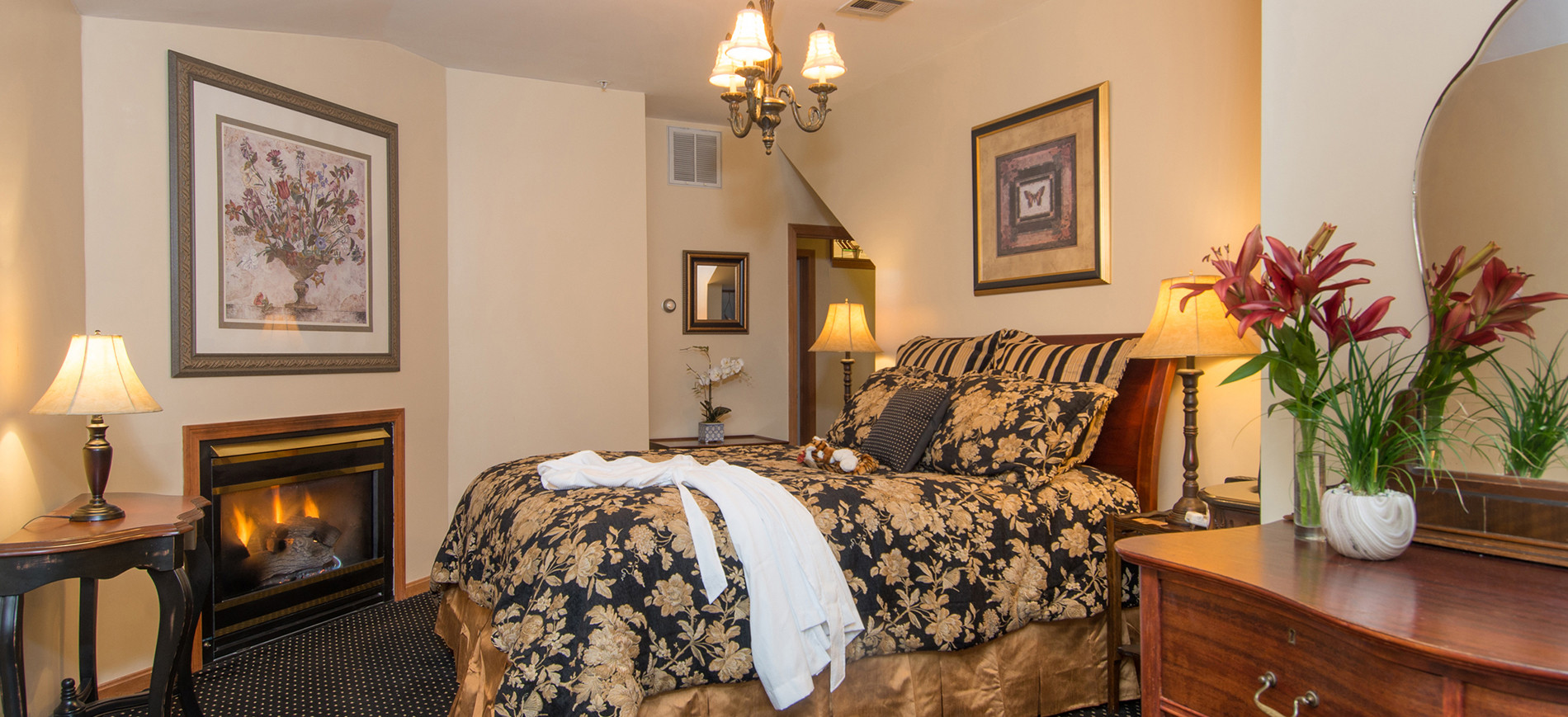 Fireplace with picture above, queen bed with gold & black bedding & white robe below chandelier