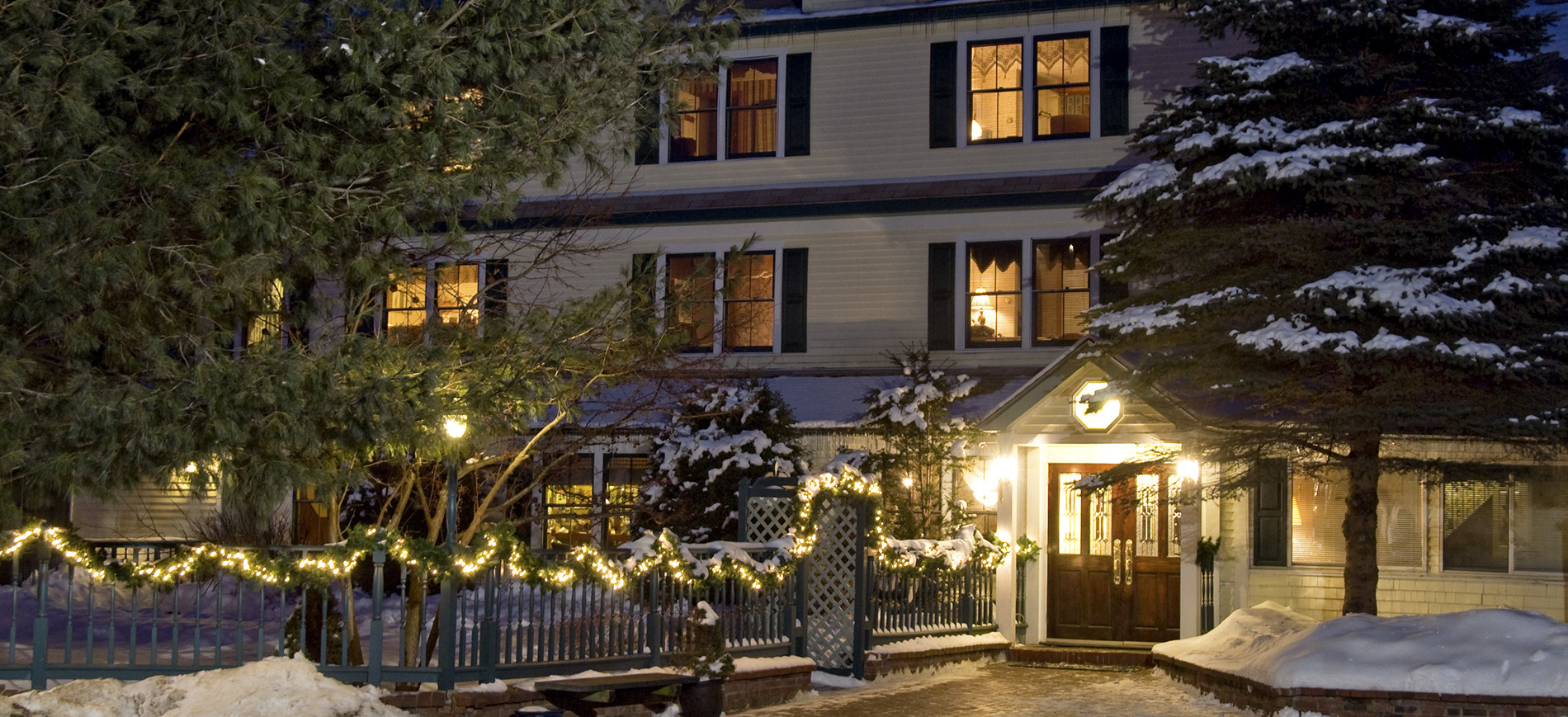 Inn at Ellis River entrance on winter night with snow