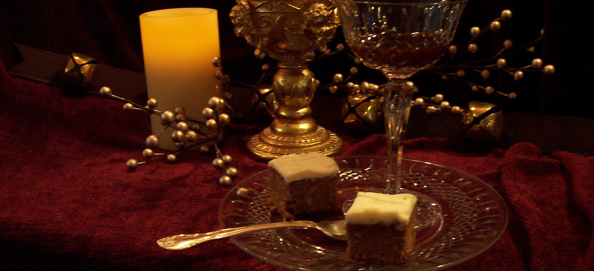Burgundy velvet cloth with pillar candle, gold goblet, champagne coupe, lebkuchen brownies on glass plate with fork