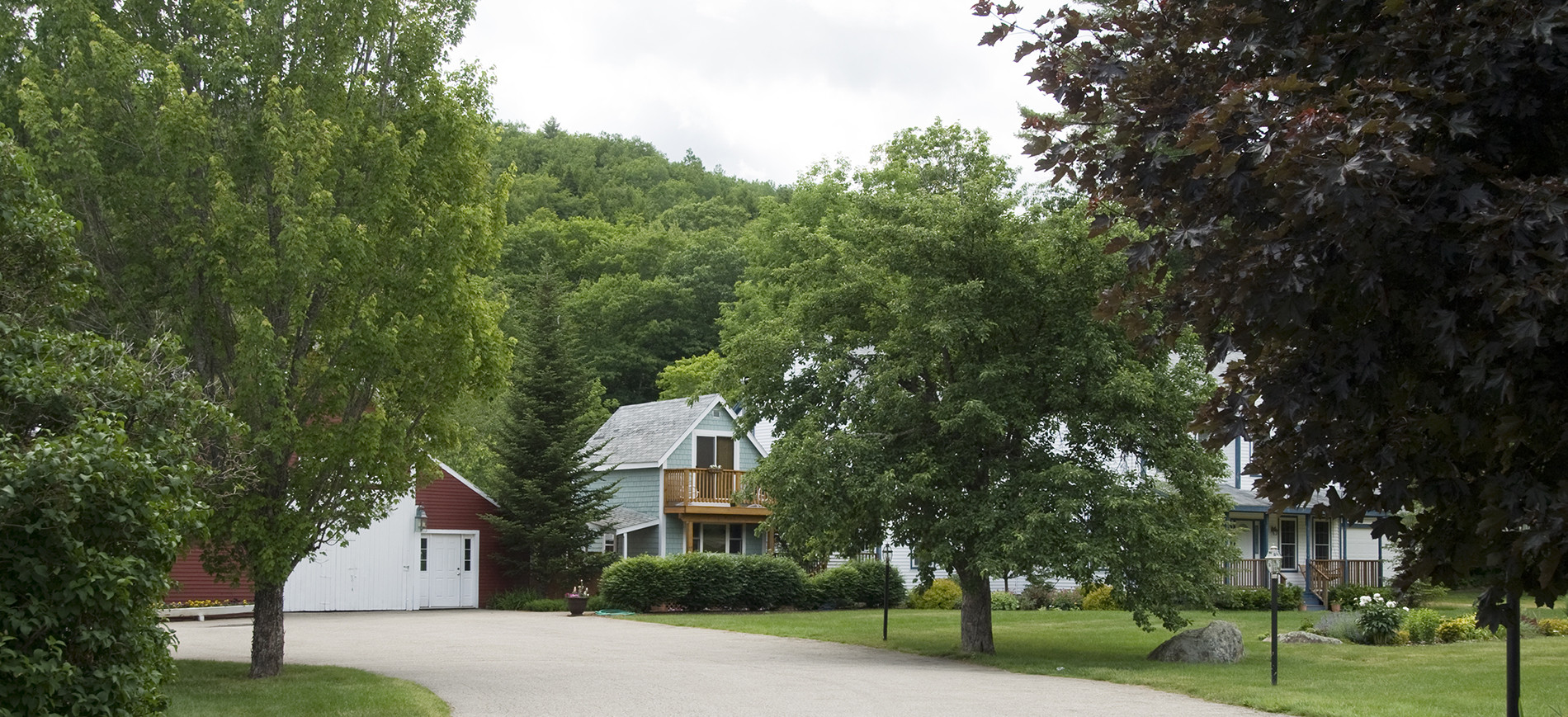 Entrance drive to Inn at Ellis River with Inn, red barn, cottage & trees